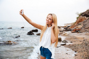 Young smiling beautiful woman listening music and making selfie while standing on the rocky beach