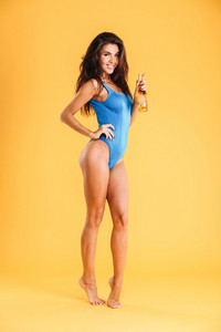 Young smiling beutiful girl in swimsuit posing and holding glass bottle isolated on the orange background