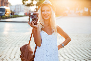 Young smiling blonde girl in hat holding retro camera while standing on the street