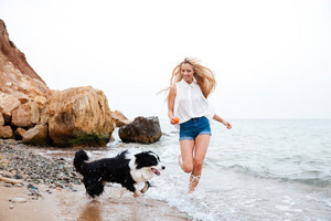 Young smiling blonde girl running with her dog on the beach