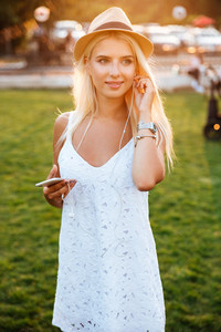 Young smiling blonde woman listening music with earphones and smartphone at the park