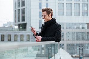 Young smiling business man in glasses looking at phone and holding coffee in hand outdoors