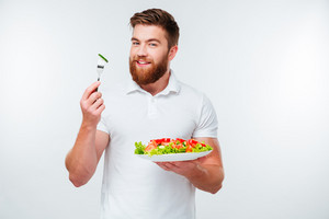 Young smiling businessman holding fork to eat fresh vegetable salad meal isolated on white background