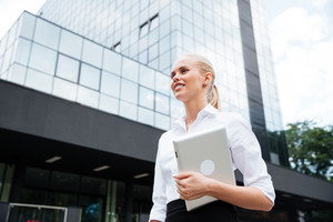 Young smiling businesswoman holding digital tablet while looking away against office building