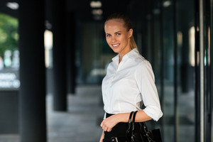 Young smiling businesswoman standing and holing handbag outdoors