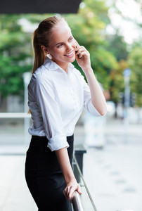 Young smiling businesswoman talking in the mobile phone outdoors