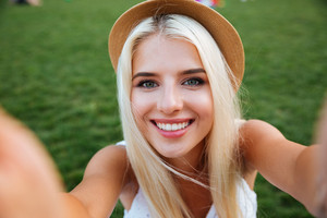 Young smiling cheerful blonde girl in hat making selfie while standing on the street