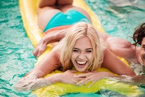 Young smiling cheerful girl lying on an inflatable mattress in the pool with friends