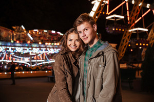 Young smiling couple in amusement park. in warm clothes looking at the camera