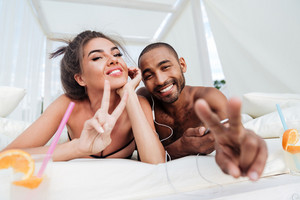 Young smiling happy couple laying on the beach bed and showing victory sign outdoors