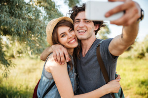 Young smiling happy couple with backpacks hiking in the forest and making selfie