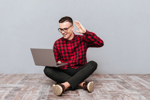 Young Smiling hipster in glasses sitting on the wooden floor with laptop and waving in camera of laptop. Isolated gray background