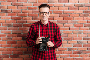 Young smiling Hipster in red shirt standing near the wall with retro camera.