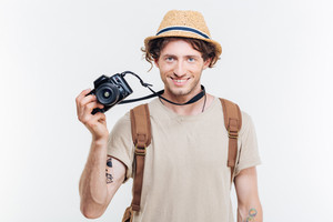 Young smiling man holding retro camera isolated on a white background