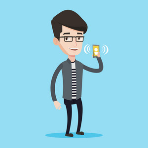 Young smiling man holding ringing mobile phone. Happy man answering a phone call. Man standing with ringing phone in hand. Vector flat design illustration isolated on blue background. Square layout.