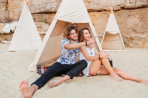 Young smiling man pointing finger at something while sitting at the beach with his girlfriend