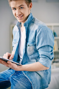 Young smiling man using touchpad