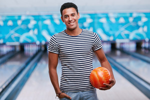 Young smiling man with ball in bowling club
