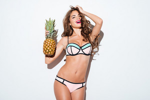 Young smiling pretty sexy girl holding pineapple and posing isolated on the white background