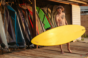 Young smiling professional surfer holding surf board at the shack