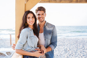 Young smiling romantic couple in love standing together at the beach