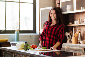 Young Smiling Woman in red shirt standing at the table in kitchen and looking at camera. Side view