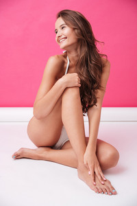 Young smiling woman in white swimsuit sitting and looking away over pink background