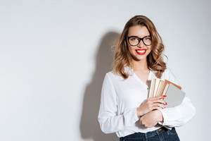 Young smiling woman standing and holding a book on white background