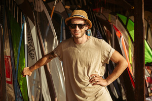 Young smiling young man in hat and sunglasses standing at the surf shack