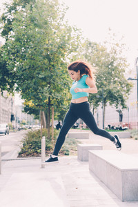 Young sportive woman jumping looking at camera outdoor in the city - athletic, sportive, succesful concept