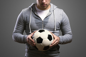 Young sportsman holding a soccer ball. Studio shot on gray background.
