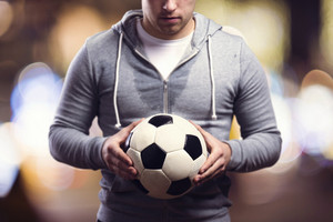 Young sportsman in the night city holding a soccer ball