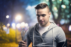 Young sportsman jogging in the night city with a water bottle