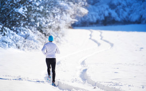 Young sportsman jogging outside in sunny winter park