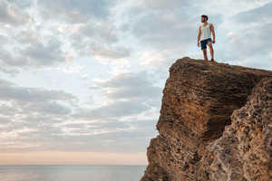 Young sportsman standing on the mountain rock by the sea and looking at sunset