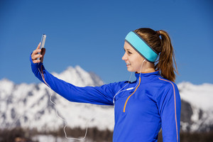 Young sportswoman jogging outside in sunny winter mountains