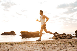 Young sporty man athlete running at the rocky beach at the sunset