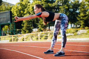 Young sporty woman stretching on a track at the stadium outdoors