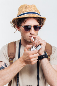 Young stylish man with retro camera smoking cigarette isolated on a white background