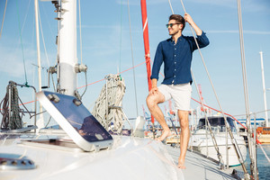 Young stylish sailor man in hat and sunglasses standing on the yacht
