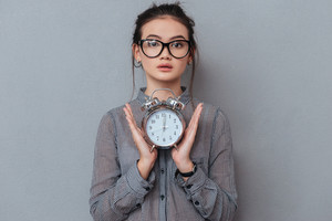 Young surprised asian woman in glasses and shirt holding the clock in hands. Isolated gray background
