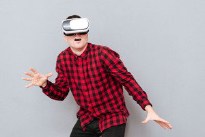 Young surprised Hipster in virtual reality device in studio. Isolated gray background