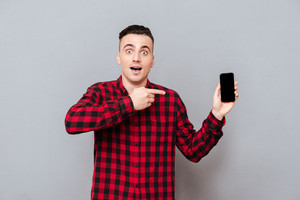 Young surprised man in shirt showing blank smartphone screen and pointing on him. Isolated gray background