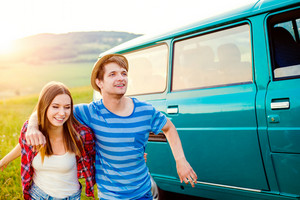Young teenage couple in love, boy and girl, boyfriend and girlfriend, running outside in green nature, old green campervan