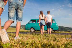 Young teenage couples in love, boy and girl, boyfriend and girlfriend, outside in green grass, against blue sky, old campervan, back view, rear viewpoint