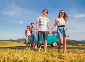 Young teenage couples in love, boy and girl, boyfriend and girlfriend, outside in green nature, against blue sky, old green campervan