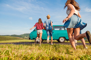 Young teenage couples in love running, boy and girl, boyfriend and girlfriend, outside in green nature, against blue sky, old campervan, back view, rear viewpoint