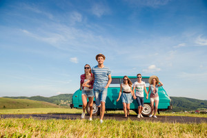 Young teenage couples in love running, boy and girl, boyfriend and girlfriend, outside in green nature, against blue sky, old campervan