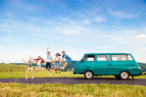 Young teenage hipster frieds with campervan against green nature and blue sky, jumping