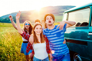 Young teenage hipster frieds with campervan having fun, against green nature and blue sky, hands up, arms raised